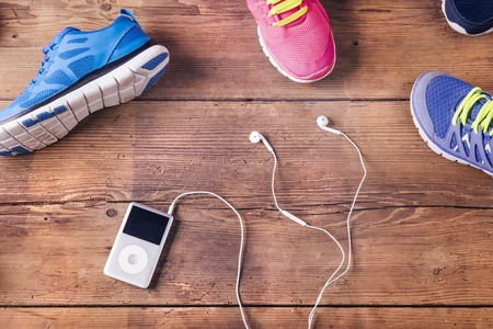 Various running shoes and mp3 player laid on a wooden floor background