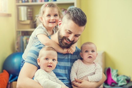 Photo pour Young hipster father hugging his cute little daughters - image libre de droit