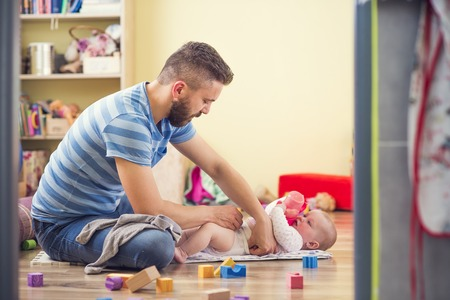 Photo pour Young hipster father changing nappy to his little baby daughter - image libre de droit
