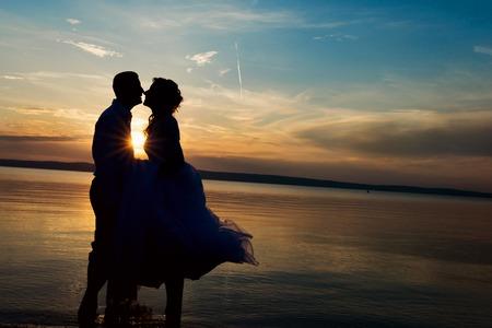 Foto de Beautiful young wedding couple standing on the beach - Imagen libre de derechos