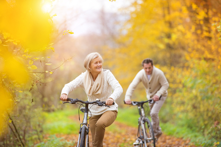 Active seniors riding bikes in autumn nature. They having romantic time outdoor.