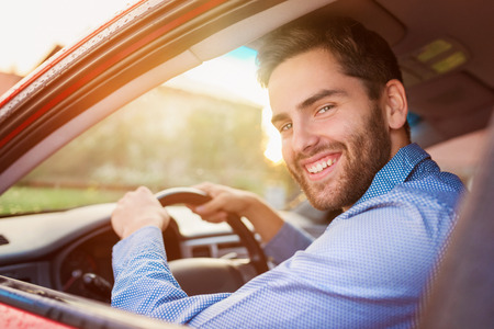Foto de Handsome young man in a blue shirt driving a car - Imagen libre de derechos