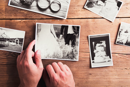 Foto de Wedding photos laid on a table. Studio shot on wooden background. - Imagen libre de derechos