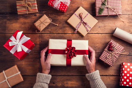 Photo pour Man holding Christmas presents laid on a wooden table background - image libre de droit
