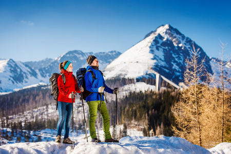 Photo pour Young couple hiking outside in sunny winter mountains - image libre de droit