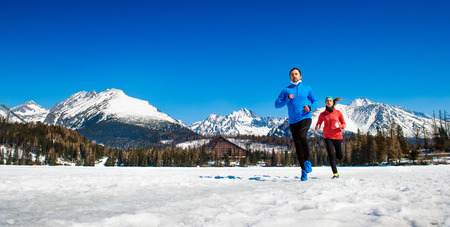 Foto de Young couple jogging outside in sunny winter mountains - Imagen libre de derechos