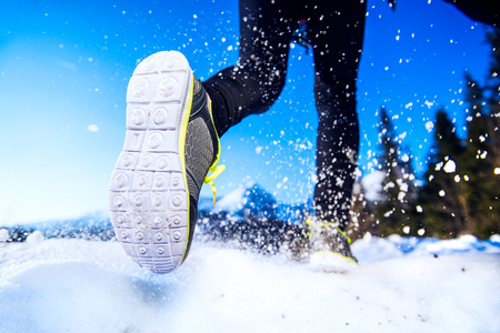 Photo pour Legs of a young runner outside in winter nature - image libre de droit