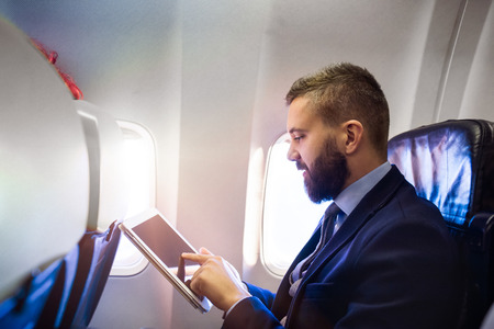 Photo pour Young handsome businessman with tablet sitting inside an airplane - image libre de droit