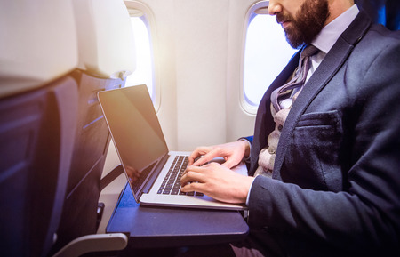 Photo pour Unrecognizable young businessman with notebook sitting inside an airplane - image libre de droit