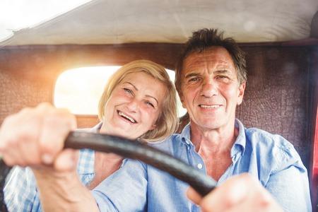 Foto de Senior couple in their vintage red car - Imagen libre de derechos