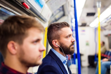 Two young handsome men travelling by subway