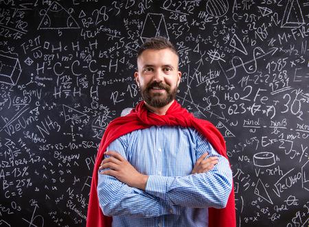 Foto de Hipster teacher in red cape standing against big blackboard with mathematical symbols and formulas. Studio shot on black background. - Imagen libre de derechos