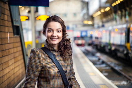 Young woman in checked brown winter coat waiting on train station