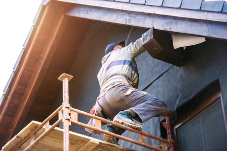 Photo pour Construction worker standing on scaffold thermally insulating house facade with glass wool and black foil. - image libre de droit