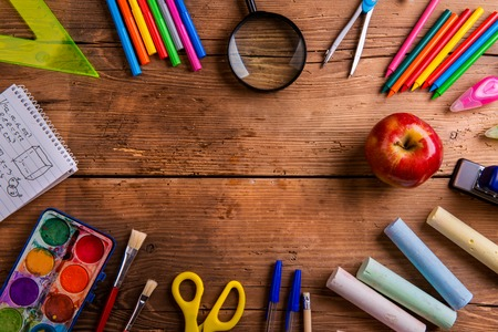 Foto de Desk with various school supplies. Studio shot on wooden background, frame composition, empty copy space - Imagen libre de derechos