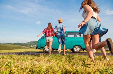 Foto de Young teenage couples in love running, boy and girl, boyfriend and girlfriend, outside in green nature, against blue sky, old campervan, back view, rear viewpoint - Imagen libre de derechos