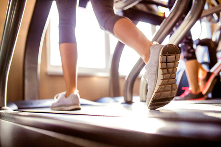 Close up of legs of woman running on treadmills gym, sunny day