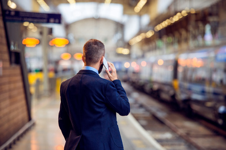 Foto per Hipster businessman with smartphone, making a phone call, waiting at the train station platform, back view, rear, viewpoint - Immagine Royalty Free