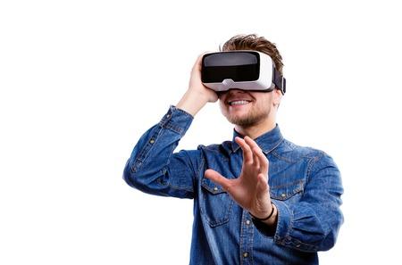 Photo pour Hipster man in denim shirt wearing virtual reality goggles. Studio shot on white background - image libre de droit