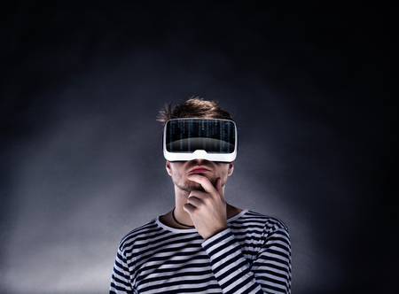 Photo pour Hipster man in striped black and white sweatshirt wearing virtual reality goggles. Studio shot on black background - image libre de droit