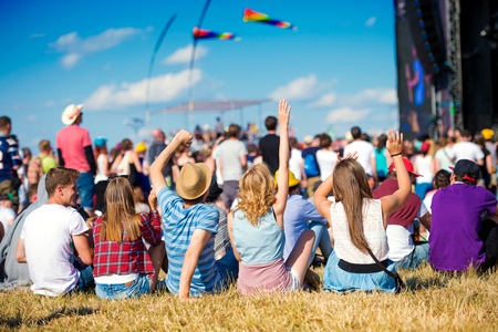 Group of teenagers at summer music festival, sitting on the grass in front of stage