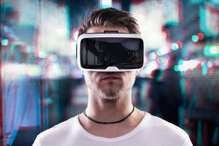Man wearing virtual reality goggles against illuminated night city