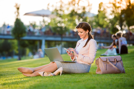 Foto per Beautiful young businesswoman sitting in a park on the grass during a lunch break, checking her smartphone, sunny summer day. - Immagine Royalty Free