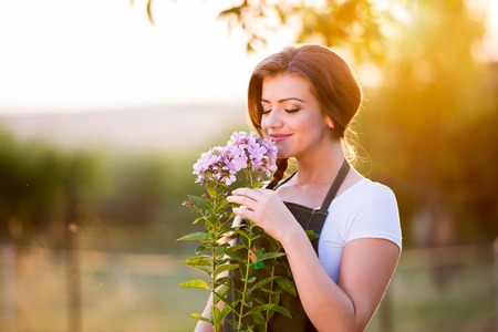Young gardener in her garden smelling flowers, green sunny nature at sunset