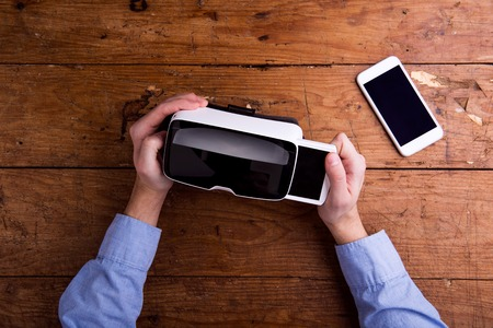 Photo pour Hands of man holding virtual reality goggles and smart phone. Flat lay. Studio shot on wooden background. - image libre de droit