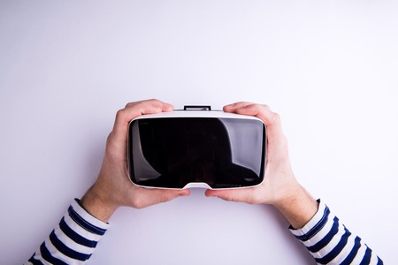 Photo pour Hands of man holding virtual reality goggles. Flat lay. Studio shot on gray background. - image libre de droit