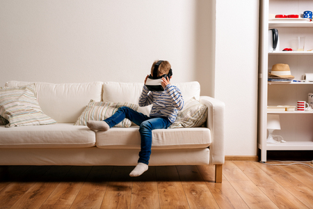 Photo pour Little boy in striped t-shirt wearing virtual reality goggles, sitting on white couch in a living room - image libre de droit
