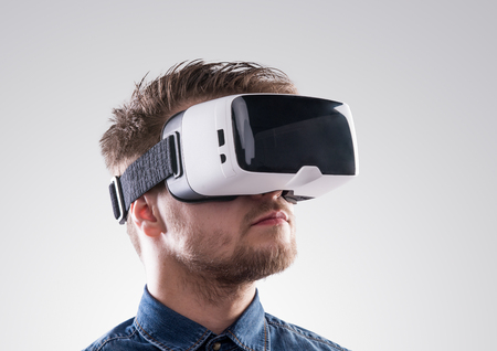 Photo pour Hipster man in denim shirt wearing virtual reality goggles. Studio shot on gray background - image libre de droit