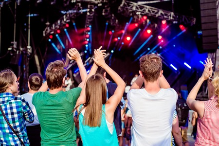 Teenagers at summer music festival against the stage in a crowd enjoying themselves, clapping, back view