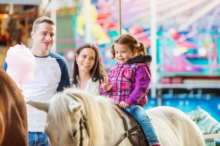 Little girl enjoying a ride on pony at fun fair, parents watching her, amusement park