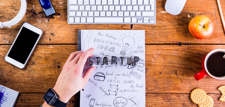 Photo for Business person at office desk working. Smart watch on hand and smart phone on the table. Start up sign made of cookie cutters. Coffee cup, notepad and various office supplies around the workplace. Flat lay. - Royalty Free Image