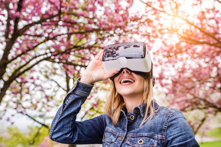 Photo pour Blond woman wearing virtual reality goggles outside in spring nature - image libre de droit
