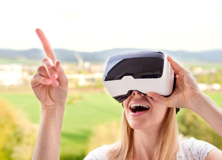 Photo pour Blond woman wearing virtual reality goggles standing in a kitchen - image libre de droit