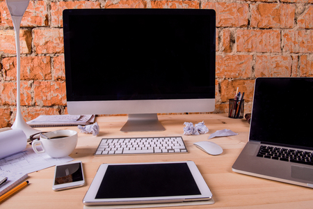 Photo for Desk with various gadgets and office supplies. Computer, smart phone, tablet and other devices and stationery around the workplace. - Royalty Free Image