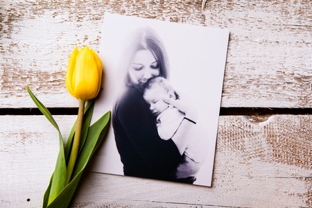 Foto de Mothers day composition. black-and-white picture of mother holding her little baby, yellow tulip. Studio shot on wooden background. - Imagen libre de derechos