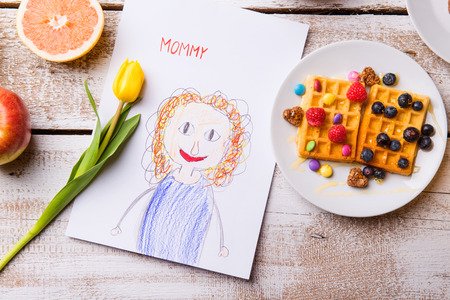 Foto de Mothers day composition. Childs drawing of her mother, yellow tulip and breakfast waffles with fruit. Studio shot on wooden background. - Imagen libre de derechos