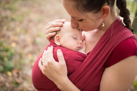 Foto de Mother carrying her cute baby daughter in sling, kissing her, outside in autumn nature - Imagen libre de derechos