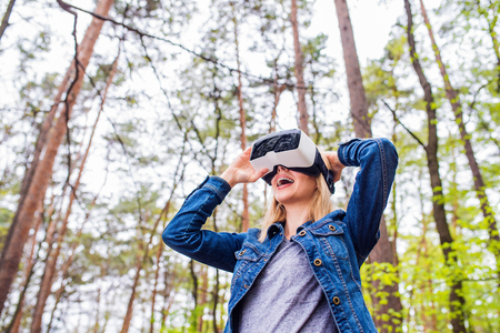 Photo pour Blond woman wearing virtual reality goggles outside in green forest, spring nature - image libre de droit