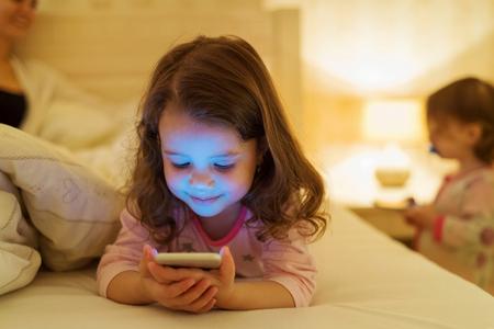 Foto de Cute little girl with smartphone lying in a bed, bedtime - Imagen libre de derechos