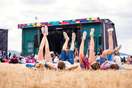 Legs of teenagers at summer music festival, lying on the grass in front of stage, rear view