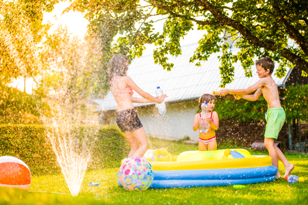 Photo pour Unrecognizable boy splashing girls with water gun in garden swimming pool, sunny summer day, back yard - image libre de droit