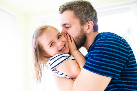 Photo for Close up of hipster father kissing his little daughter, sunny day - Royalty Free Image