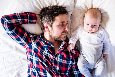 Foto de Cute newborn baby boy lying on a bed, next to his father - Imagen libre de derechos