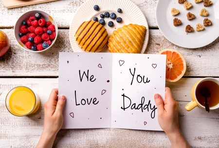 Foto de Fathers day composition. Hands of unrecognizable man holding greeting card with We love you, Daddy, text. Breakfast meal. Studio shot on wooden background. - Imagen libre de derechos