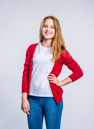 Teenage girl in jeans and red cardigan, young woman, studio shot on gray background