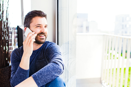 Photo for Businessman in blue long sleeved t-shirt working from home, holding smartphone, making phone call - Royalty Free Image